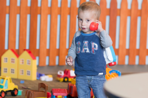 A young boy playing with a toy telephone
