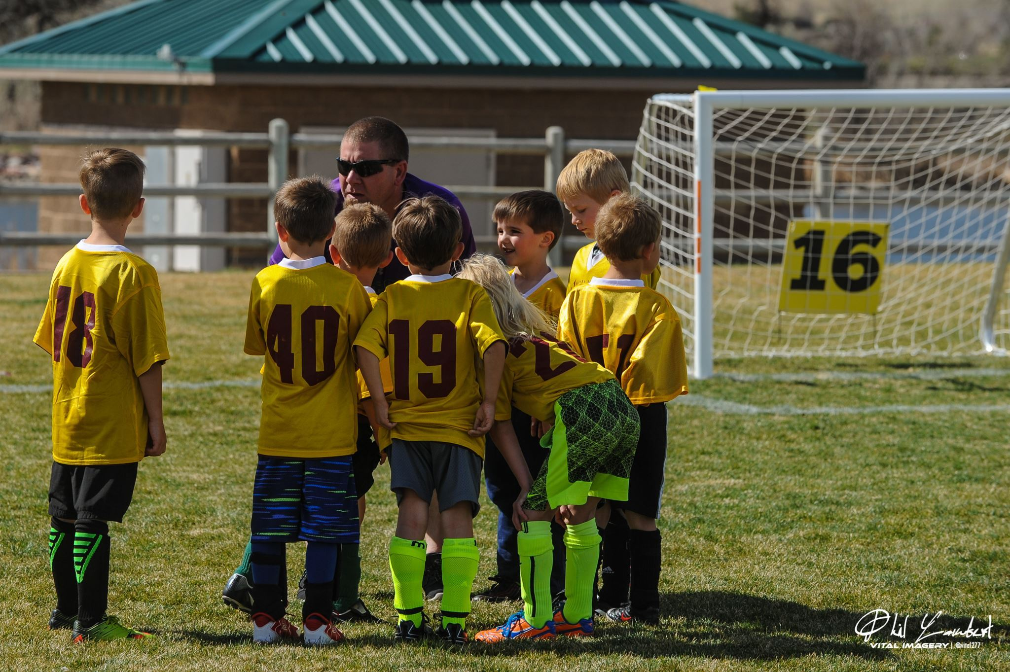 A coach huddled up with a young soccer team