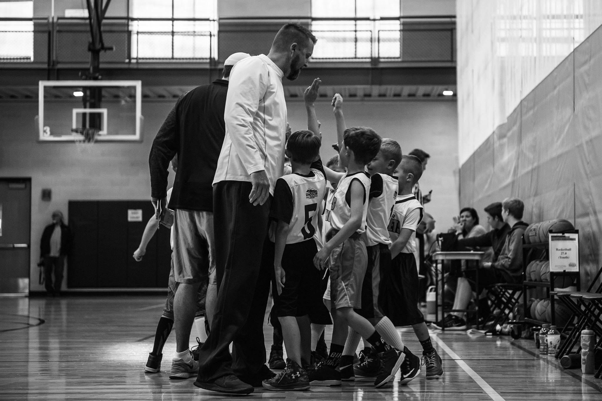 A coach and a young basketball team in a huddle