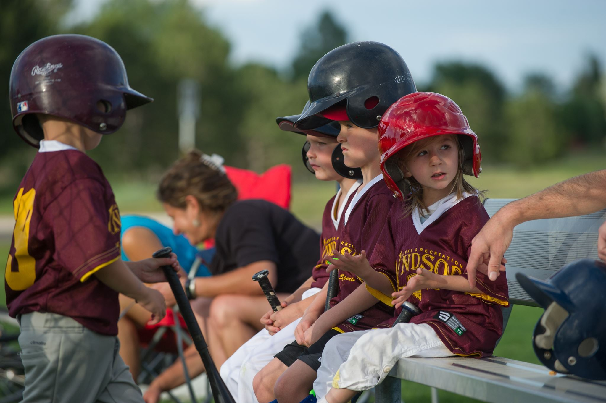 Kids Sitting on Bench with Batting Helmets On