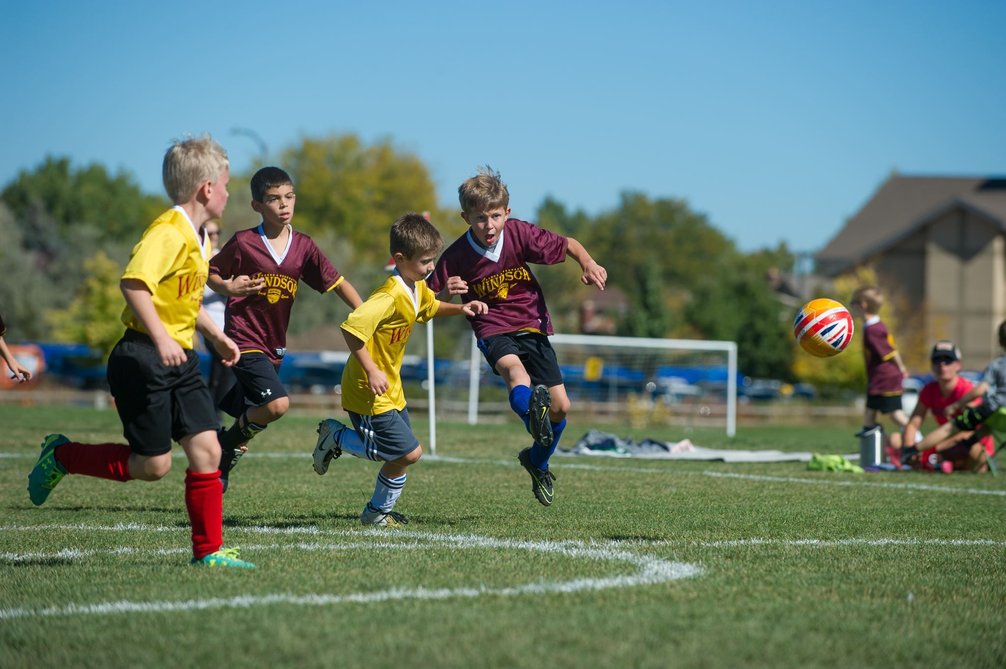 Boys Run on Soccer Field Toward Soccer Ball
