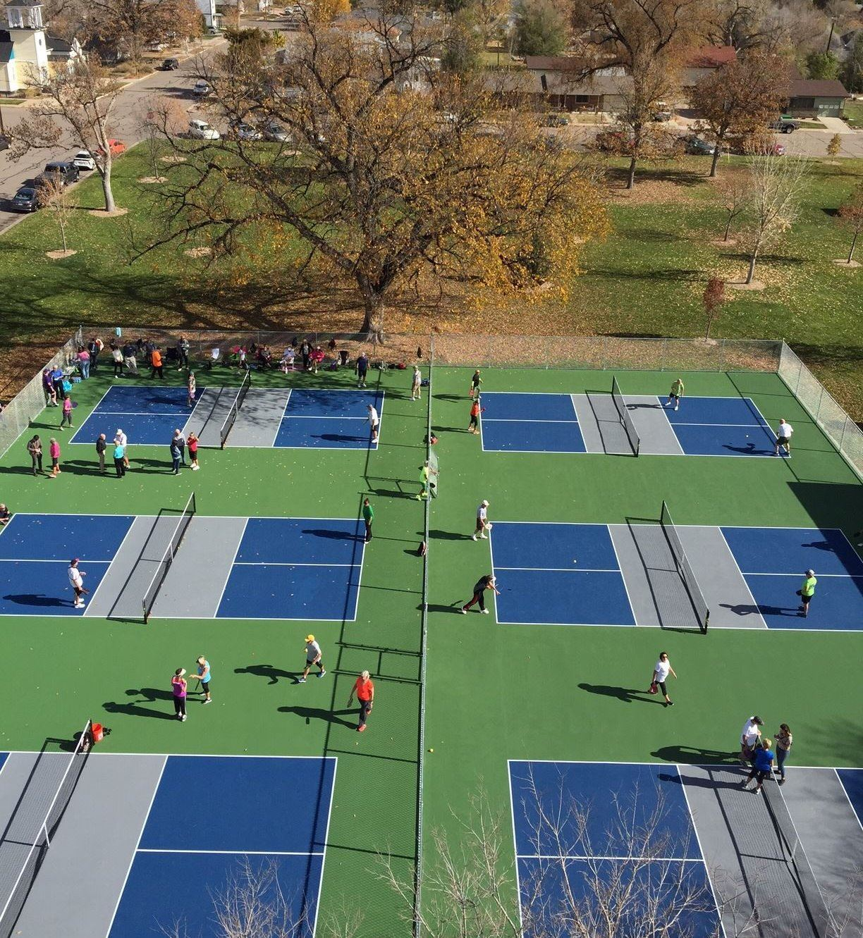 Several outdoor pickleball courts in a city park
