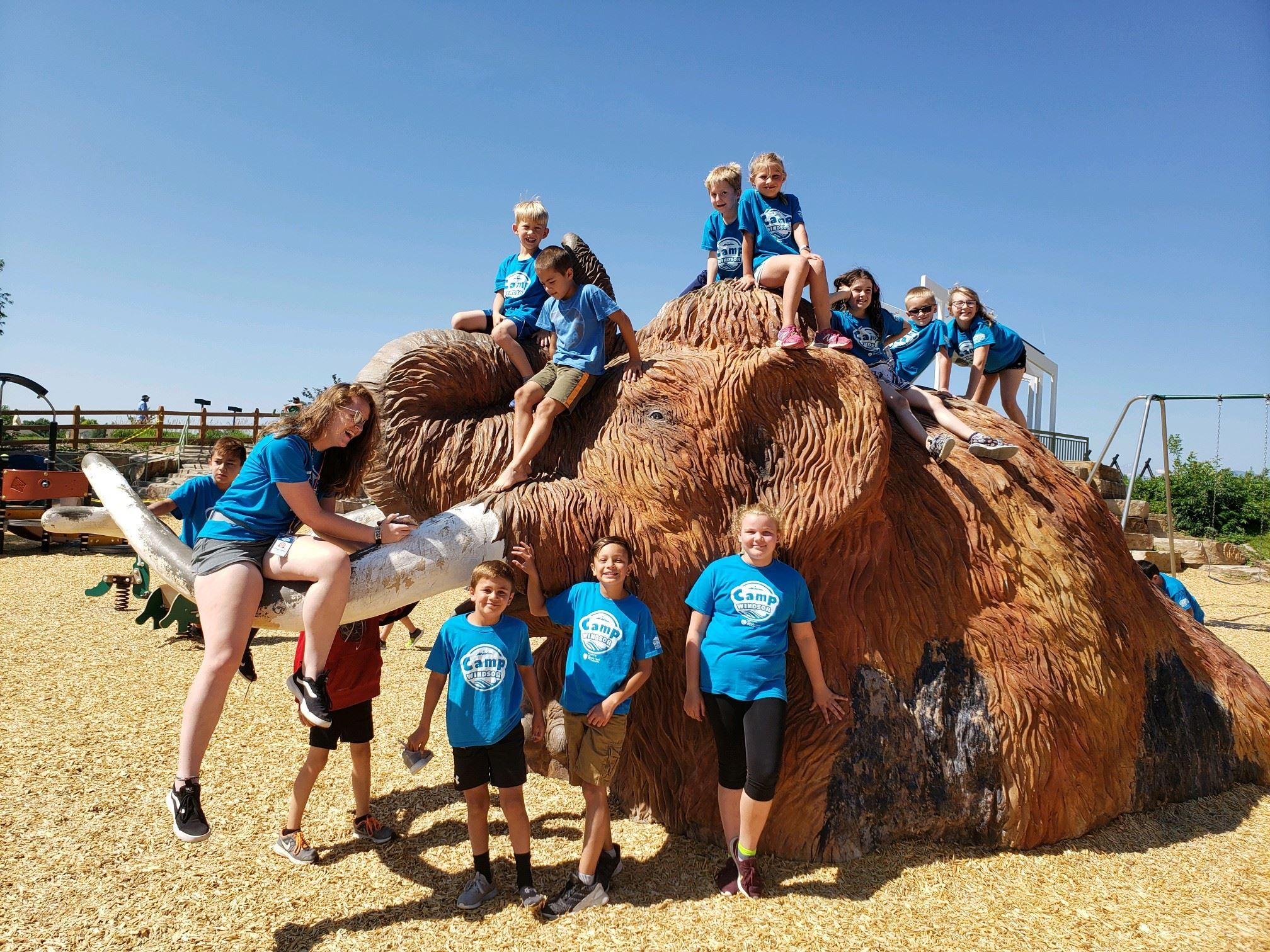 A group of children clclimbing on a large sculpture of a mastadon